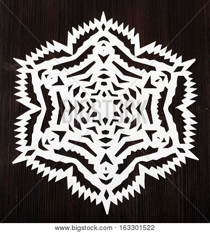 Snowflake Cut Out Of Paper On Dark Brown Plank