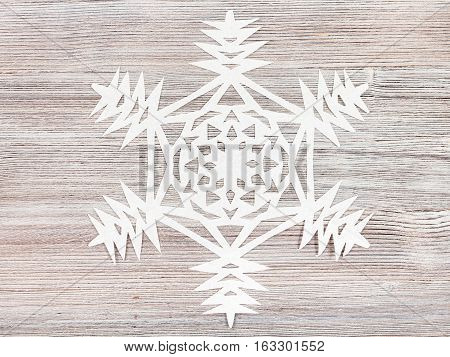 Snowflake Carved From Paper On Light Brown Board
