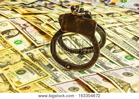 Ferrous metal handcuffs hanging on currency notes