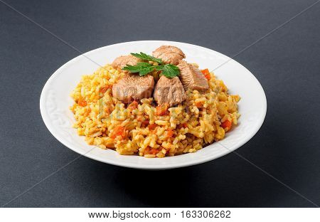 Fragrant Pilau. Pilaf fried rice with meat and vegetables on a white plate. Isolated on gray.