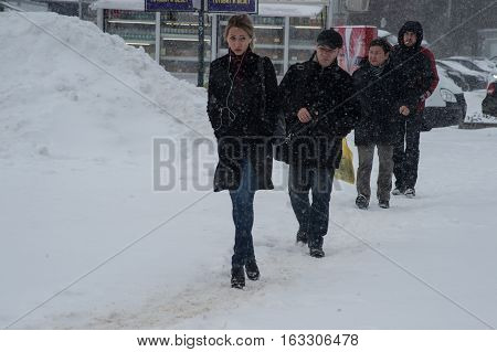 Saint-Petersburg Russia - November 8 2016: Snowfall in the city streets. Citizens are on the beaten track in the snow