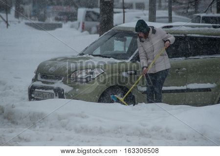 Saint-Petersburg Russia - November 8 2016: Snowfall in the city streets. Girl takes the snow from her parked car
