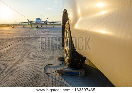 Car or Vehicle Wheel Chock for Pause Aeroplane Safety in The Airport.Aeroplane Wheel Chock made from Black Wood with Aeroplane or Airplane Background.