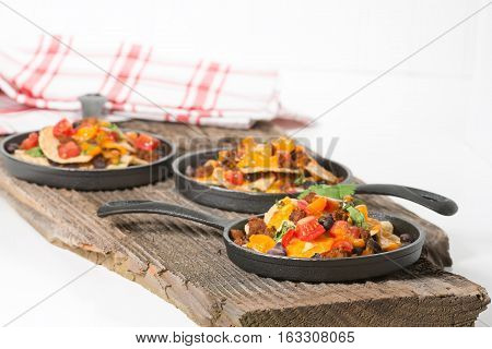 Colorful nachos served on individual cast iron fry pans.