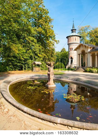 Garden pond with small statue at Orangerie of Sychrov Castle. Park water tower on the background. Bohemian Paradise, Northern Bohemia, Czech Republic