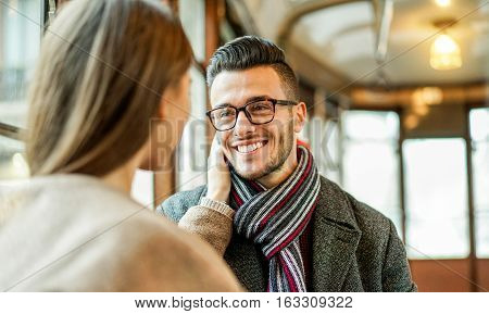 Young couple having tender moments inside old style tram bus - Girlfriend cuddling his boyfriend indoor - Concept of lovesweetness and relationship - Focus on man glasses eye - Warm filter