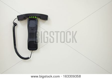 Hang up Retro style black press-button telephone mounted on a white wall.