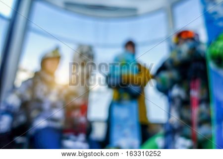 Blurred snowboarders people inside funicular cable car on top of the mountain with back sun light - Defocused image - Blurry background - Extreme sport concept - Warm vivid filter