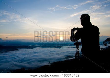 The man in the Shadow shooting Sea Fog and Sunrise with Camera and Smart Phone