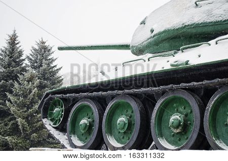 T34 tank covered with snow standing on the forest background