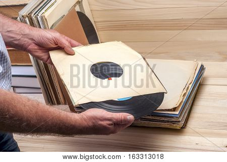 Retro styled image of a collection of old vinyl record lp's with sleeves on a wooden background. Browsing through vinyl records collection. Music background. Copy space.