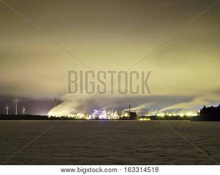 Night scene of a factory behind a frozen lake. Industrial background.