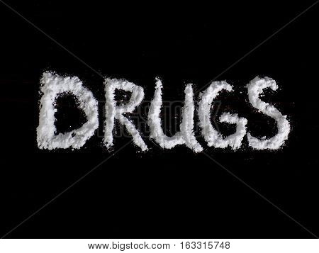 Cocaine drug powder in drugs word shaped on black background