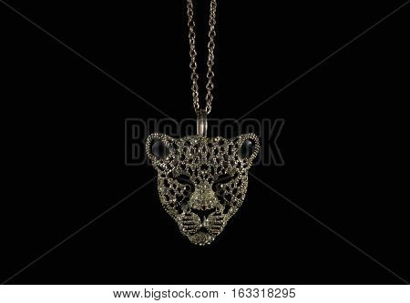 Tiger face jewelry photo. Tiger face jewelry pendant on black background photo. poster
