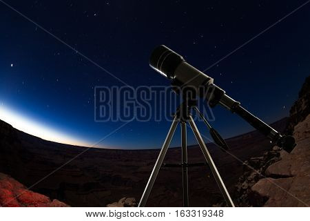 Telescope standing in the high mountains with no light pollution pointing to the stars just after dusk