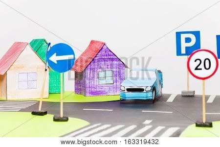 Picture of blue paper car on the parking next to the colored houses models with copy-space