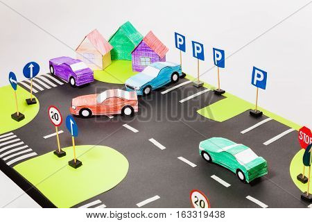 Top view of kids playing set with crosswalks, parking, paper colored cars and houses
