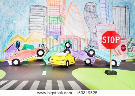 Big traffic accident at a crossing with stop road sign in the toy city made of paper