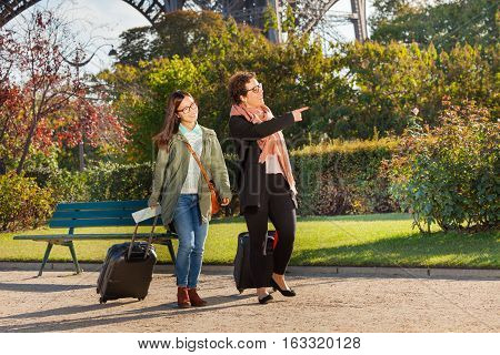 Two young women walking along Paris street and searching right way