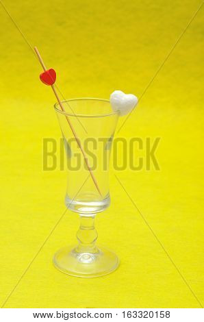 Valentine's Day. A shooter glass with a polystyrene heart on the the rim and a stick with a red heart isolated against a yellow background