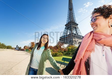 Two happy friends walking around Paris holding hands at sunny day