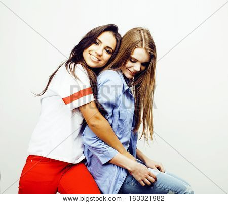best friends teenage girls together having fun, posing emotional on white background, besties happy smiling, lifestyle people concept, blond and brunette multi nations close up