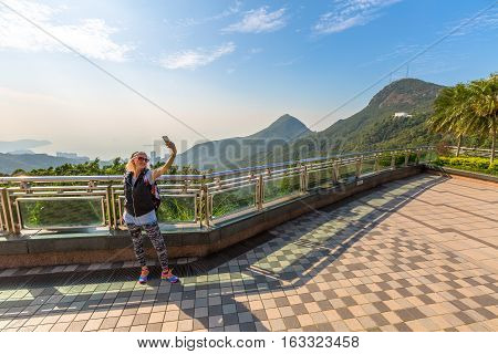 Young, smiling and fashionable tourist takes selfie on the popular free viewing terrace overlooking Victoria Peak Galleria that on the Reservoir in Hong Kong island.