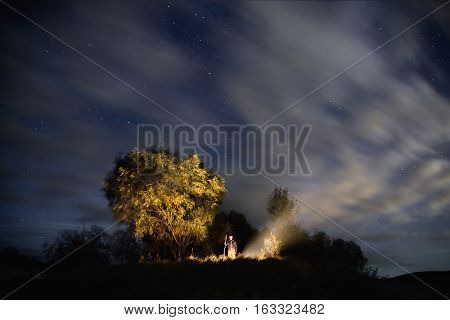 starry sky night photography astrophotography trees silhouettes clouds in the sky the man firing the fire a man stands with his stick the smoke from the fire willow