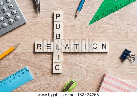 Words of public relation collected in crossword with wooden cubes