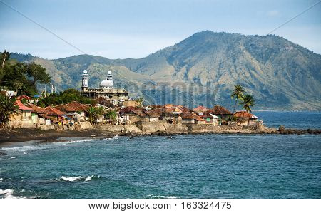 Muslim fisherman village with mosque and volcano at the background. Near Ende Flores Island Indonesia.