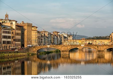 Florence, Italy-June 12, 20015.View of the Arno River and the buildings along it's banks, looking towards the Ponte Santa Trinita and Ponte Vecchio bridges in the late afternoon sunlight, Florence, Italy.
