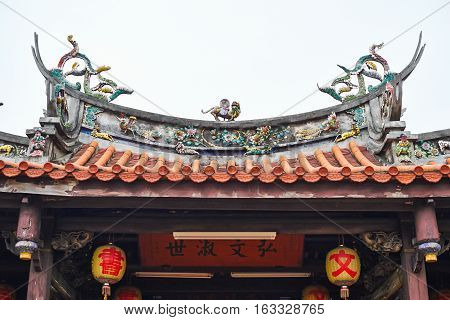 The roof of traditional oriental temple with beautiful decoration in Taiwan (Chinese Translation on lantern:Jen-wen Academy on board:improve the society by education)