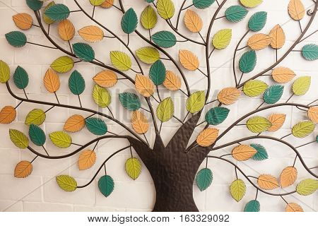 Tree with colorful leaves on white wall, stock photo