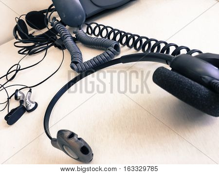 Communication technology tools background with room for copy space telephone, cords, headsets,ear buds on desk low angle view