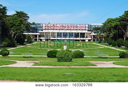 Estoril, Portugal - October 23, 2014. View of Casino Estoril with grass lawns in front of casino, vegetation, benches and statue.