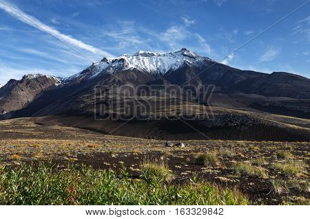 Volcanic landscape of Kamchatka Peninsula: autumn view of Kozelsky Volcano on background of blue sky beautiful clouds. Avachinsky-Koryaksky Group of Volcanoes Kamchatka Russian Far East Eurasia.