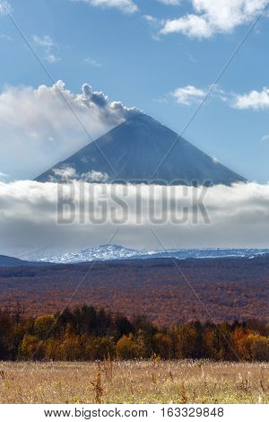 Volcanic landscape of Kamchatka: explosive-effusive eruption of Klyuchevskoy Volcano: powerful plume of gas steam ash from crater volcano. Picturesque autumn view of volcanic eruption on sunny day.