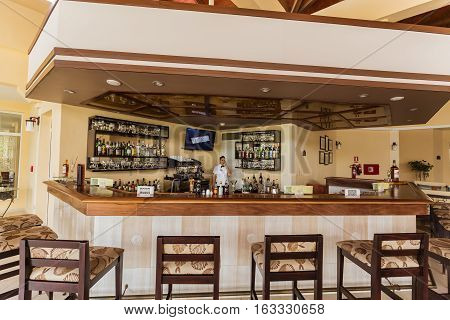 Holguing Province, Playa Pesquero hotel, Cuba, Aug. 31, 2016, gorgeous amazing inviting view of  lobby bar with young lady bartender in background at premium service section