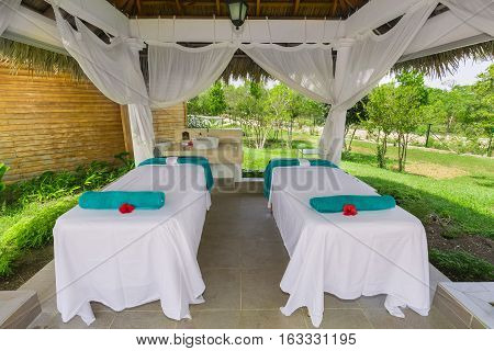 beautiful amazing inviting view of fluffy soft massage relaxing beds inside gazebo in tropical garden on sunny day
