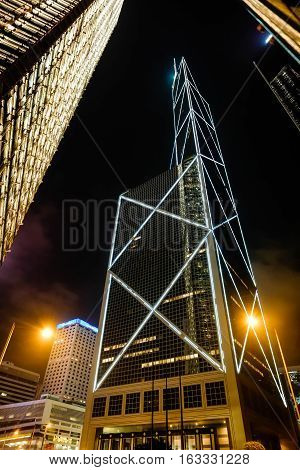 Business concept for real estate and corporate construction - looking up view in financial district the silhouettes of skyscrapers city reflect neon lights in night Hong Kong(HK) China