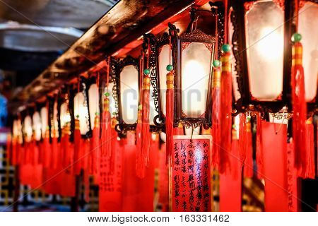 Red lantern people pray to god for blessing in traditional old oriental chinese temple in Hong Kong(HK) (Chinese Translation on paper : wish all the best for life)
