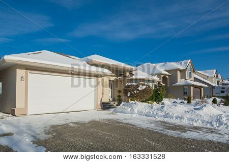 Wide garage of luxury house with driveway and front yard in snow. Street of residential houses on winter sunny day