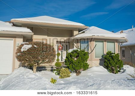 Entrance of luxury house with front yard in snow. Residential house on winter sunny day decorated for Christmas celebration