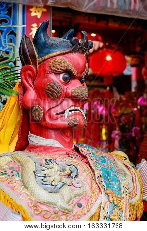 Taiwan - April 30 2016 : God statue in traditional old oriental chinese temple in Taiwan (Chinese Translation on god's strap : mazu temple on couplet : god bless people)