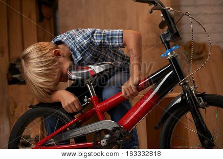 Preteen boy adjusting bicycle seat for his height