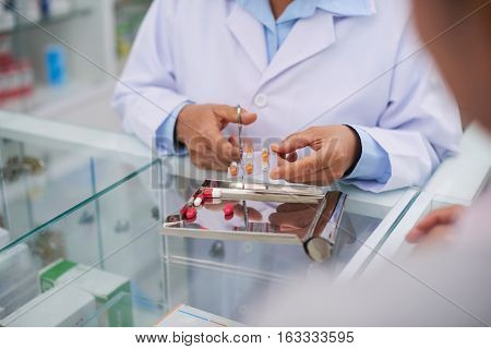 Pharmacist cutting package of pills for drugstore customer