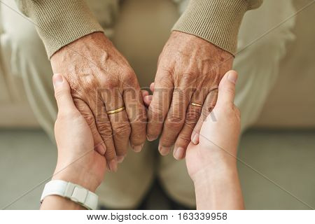 Close-up image of granddaughter holding hands of senior man