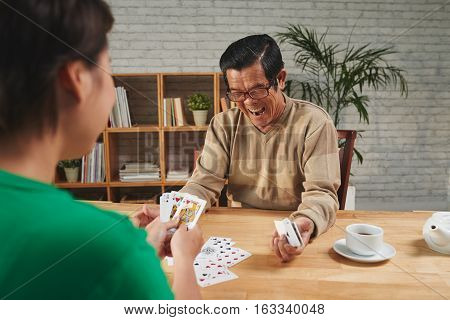 Vietnamese senior man excited to win card game
