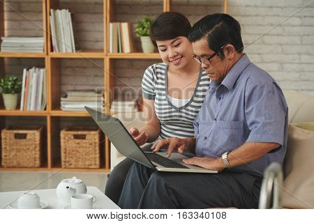Senior man and his granddaughter watching something on laptop