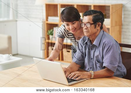 Nurse helping senior man with work on laptop